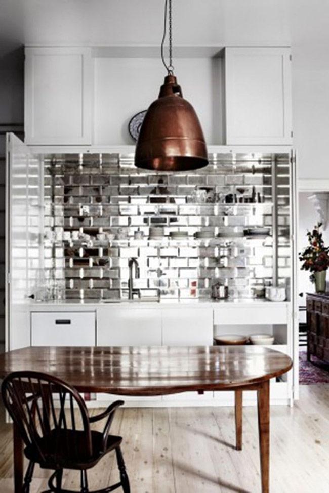 Lát backsplash (tấm chắn tường bếp) bằng gương, cụ thể là những tấm gương hình chữ nhật nhỏ là cách tuyệt vời để 'nâng cấp' căn bếp, mang lại vẻ hiện đại và thêm ánh sáng cho căn phòng.