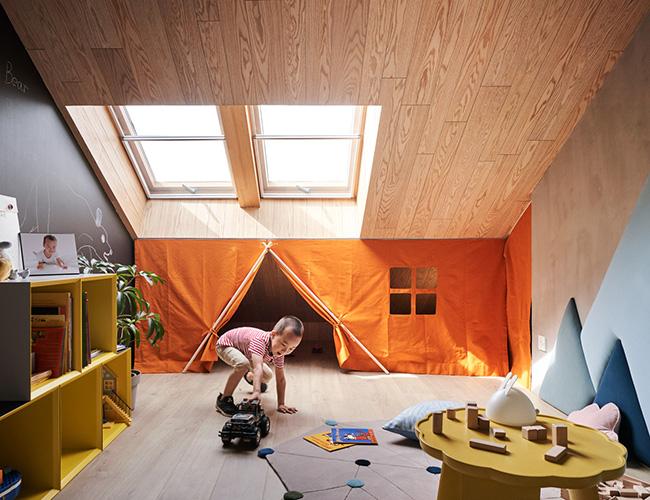 Cậu bé vui vẻ chơi đùa trong căn phòng của mình. Bên trong chiếc lều còn là cả một không gian bí mật rộng rãi.